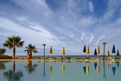 A resort image with sky, water and palms Royalty Free Stock Photography