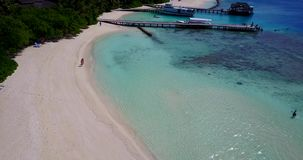 Resort in Maldives white sand beach tropical islands with drone aerial flying birds eye view with aqua blue sea. Water and sunny sky stock footage
