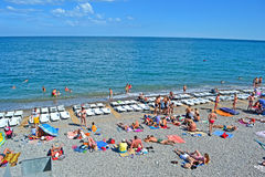 Resort, people on the public pebble beach near Bla Stock Image