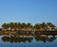 Resort places. Palm trees, canopies and fungi for suntan are located on the coast and are reflected in water Stock Image