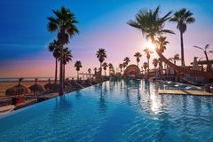 Resort pool in a beach with palm trees sunrise. Resort pool in the beach with palm trees at sunrise Stock Photo