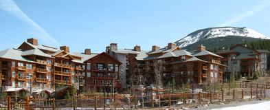 Resort in Rocky mountains. Wide angle view of tourist accommodation with snow capped Rocky mountains in background, Canada Royalty Free Stock Photography