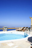 Resort, Santorini Island, Greece. Scene of swimming pool overlooking view of coastline, resort at Santorini Island, Greece Stock Photos