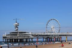 View from the beaches of Scheveningen of the Pier with bungyjumo- and zipline attraction stock photography