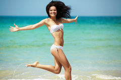 Resort, sea and health body. Young happy girl running on beach. Happy woman in white bikini swimwear open her heart to sun. Vacation, beautiful sea and natural Stock Image