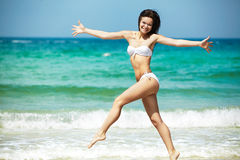 Resort, sea and health body. Young happy girl running on beach. Happy woman in white bikini swimwear open her heart to sun. Vacation, beautiful sea and natural royalty free stock photography