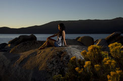 Resort Sunset. A young girl sits on the rocks along the Lake Tahoe shoreline at sunset. Beautiful dramatic lighting evokes many moods. Plenty of negative space royalty free stock photo