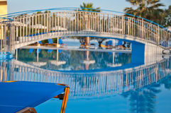 Resort with swiming pool. Swiming pool  with bridge for recreation surrounded by palm trees and sun loungers Stock Photography