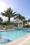 Resort Swimming pool. Tropical resort swimming pool in south Florida. Blue pool with waterfall surrounded by palm trees and cabanas Stock Photo