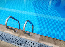 Resort swimming pool design. An image showing the pool ladder and geometric design of a resort pool, with blue colour tiles under water and carved stone details royalty free stock photo