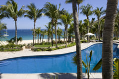 Resort Swimming Pool and Ocean View. Resort swimming pool patio looking out towards sea Stock Photo