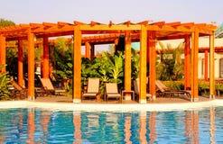 Resort swimming pool, wood pergola and deck chairs stock image