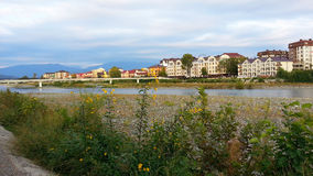 The resort town Adler on the banks of the Mzymta river. Autumn flowers on the shore, a bridge across the river, houses, hotels, cottages and mountains on the Stock Photography