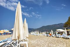 Resort tropical beach. Summer vacation. Umbrellas and sunbeds on white sand. Alanya, Turkey. Stock Image