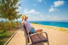 Resort vacation theme. Girl sitting on bench on seaside with amazing view at the sea Stock Photography