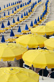 Resort waiting for tourists. Sand beach full of sunbeds and umbrellas Stock Photos