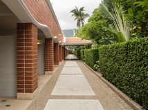 Resort way between brick wall and garden Stock Images