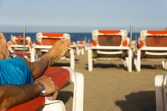 Man tanning with all inclusive bracelet on orange hammock on the beach. Resort, wristband, summer vacation, travel holidays, sun tan, skin care, relax concepts stock image