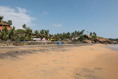 Resorts and Trees in Beach. Rocks at the sandy beach of Kovalam in Thiruvananthapuram, Kerala. A part of a beach resort is also seen with green trees. On the stock photos