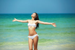 Resorts, vocation, sea and health body. Young happy girl have rest on beach. Happy woman in white bikini swimwear open her heart to sun. Vacation, beautiful sea Stock Images