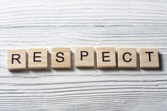 RESPECT word written on wood block ta wooden background.  Stock Photography