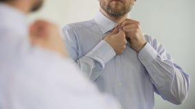 Respectabele bedrijfdirecteur die op middelbare leeftijd grondig voor het werk, spiegel voorbereidingen treffen stock footage
