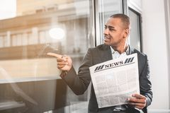Respectable African businessman resting with print media. Waist up portrait of perspective young man sitting near window. Guy looking at the street through glass royalty free stock image