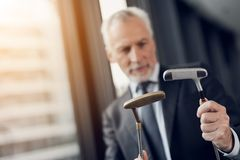 A respectable elderly man playing a mini golf in the office. He looks at two golf clubs and wants to choose one of them Royalty Free Stock Image