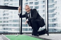 A respectable elderly man playing a mini golf in the office. He smiles and looks at the miniature golf course Royalty Free Stock Photography