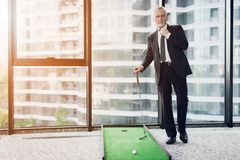 A respectable elderly man playing a mini golf in the office. He is preparing to strike Stock Photography
