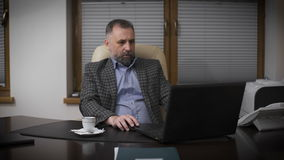 Respectable gentleman aged with graying hair. Chief in his office working with a laptop and drinking coffee stock video