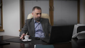 Respectable gentleman aged with graying hair. Chief in his office working with a laptop and drinking coffee