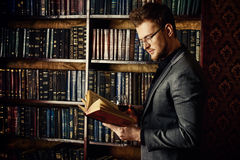 Respectable. Handsome well-dressed man stands by bookshelves in a room with classic interior. Fashion Stock Images