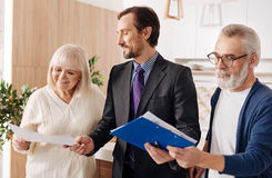 Respectable lawyer demonstrating contract for aged couple of clients Royalty Free Stock Photos
