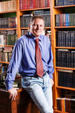Respectable man leaned on the table. In library stock photography