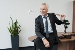 A respectable man sits on the edge of a table with a golf club behind him. A respectable elderly man is sitting in the office on the edge of the table with a Royalty Free Stock Images