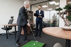 The employee came to the director with a report. Director plays golf in the office Stock Photos