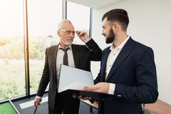 The director was playing golf in the office. The subordinate came to him with a report Stock Images
