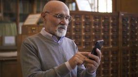 Respectable professor is using smartphone standing in university library. Respectable professor is using smartphone standing in university library, elderly stock footage