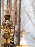 Respected angel statue with white pagoda background in Wat Phra. That Doi Gongmu in Maehongson, Thailand Stock Photo