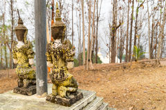 Respected angel statue with white pagoda background in Wat Phra. That Doi Gongmu in Maehongson, Thailand Royalty Free Stock Photo
