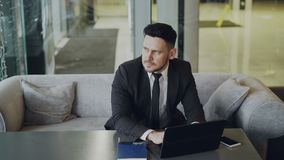 Respected Caucasian businessman in black business suit sitting and working concentrated on his laptop computer in modern. Cafe indoors stock footage