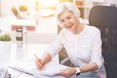 Respected competent lady checking some numbers Royalty Free Stock Photography