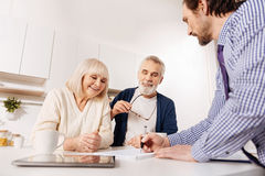 Respectful agent showing house project to aged couple of clients Royalty Free Stock Photography