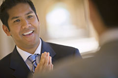 Respectful businessman greeting counterpart in building arcade, smiling (differential focus, tilt) Stock Photography
