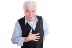 Respectful senior man with hand on chest. Isolated single mature man with smile and respectful expression gesturing as hand is on chest Royalty Free Stock Photography