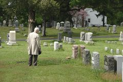 Respects 3. An elderly man pays his respects at a cemetery royalty free stock photo