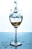 Respingo da água e das moedas em um vidro Fotografia de Stock Royalty Free