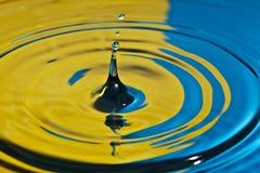 Respingo da água em amarelo e no azul Fotografia de Stock Royalty Free