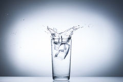 Respingo da água nos vidros isolados no branco Fotografia de Stock Royalty Free